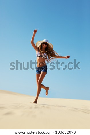 Young woman running on beach. - stock photo