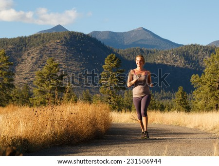 Young Woman Running on Beautiful Outdoor Trail (View of Trail) - stock photo