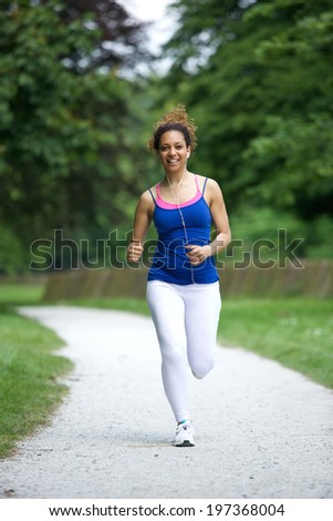 Young woman running on footpath in the park  - stock photo