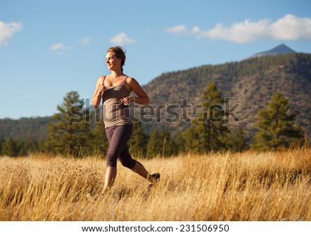 Young Woman Running on Grassy Rural Trail (Runner Leaving Frame/Emphasis on Runner) - stock photo