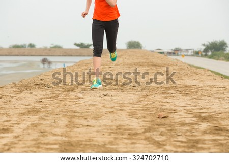 young woman running on mountain trail, closeup on leg