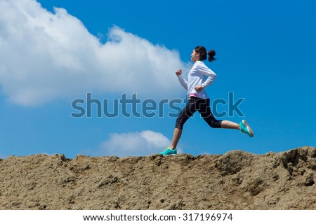 young woman running on mountain trail with blue sky and clouds background