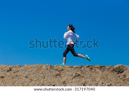 young woman running on mountain trail with blue sky background