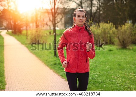 Young woman running on road in the park