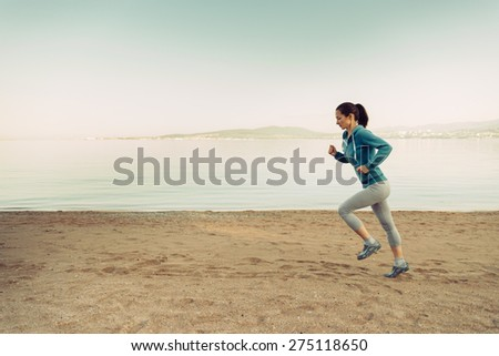 Young woman running on sand beach near the sea in summer in the morning. Concept of sport and healthy lifestyle. Space for text in the left part of image - stock photo