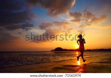 Young woman running on sea coast at sunset