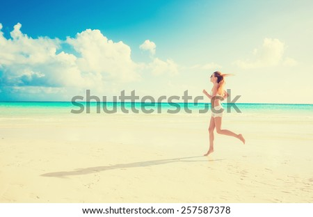 Young woman running on summer beach on the coast of the ocean blue sky background  - stock photo