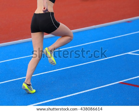 young woman running on the athletics track