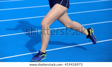 young woman running on the athletics track with blue colored lanes