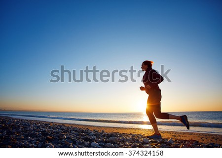 young woman running on the beach against sea and blue sky at the sunrise
