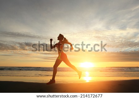 young woman running on the beach at sunrise, asian