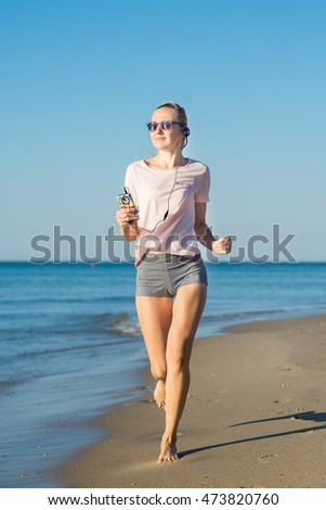 Young woman running on the beach in the morning
