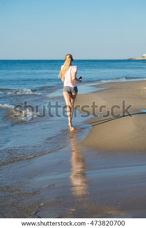 Young woman running on the beach in the morning.Back view