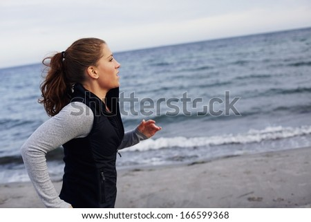 Young woman running on the seashore. Pretty young female model jogging on the shoreline. Female runner running on beach. Exercising and training. - stock photo
