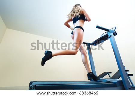 Young woman running on treadmill in gym. - stock photo