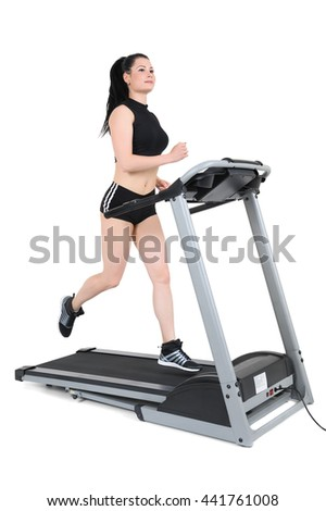 young woman running on treadmill machine, motion blur, isolated at white background - stock photo