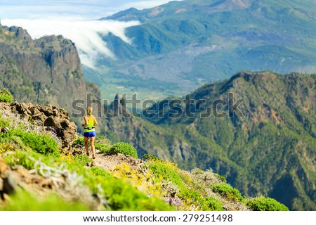 Young woman running or power walking in mountains on sunny summer day. Beautiful natural landscape and female runner jogging exercising outdoors in nature, rocky trail footpath on Canary Islands - stock photo