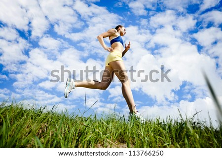 Young woman running outdoor over blue sky