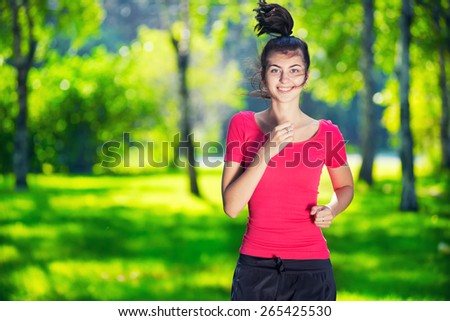 Young woman running outdoors in green park at lovely sunny summer day. Jogging - stock photo