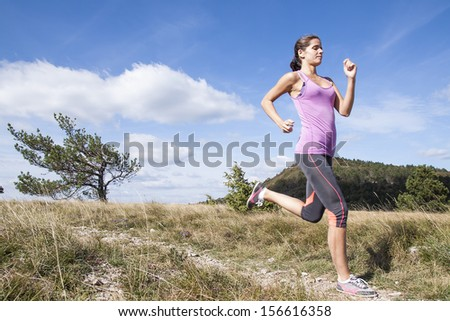 Young woman running outdoors in the nature - stock photo