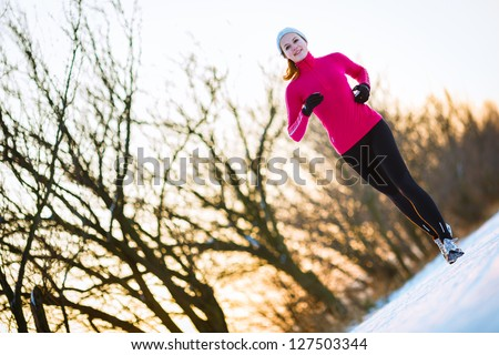 Young woman running outdoors on a cold winter day - stock photo
