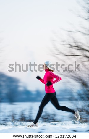 Young woman running outdoors on a cold winter day (motion blurred image) - stock photo