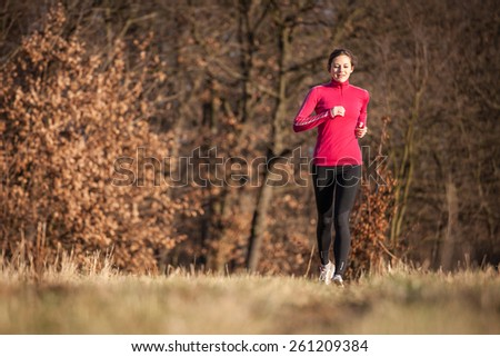 Young woman running outdoors on a lovely sunny winter/fall day - stock photo
