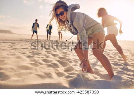 Young woman running race on the beach with friends. Group of young people playing games on sandy beach on a summer day. - stock photo