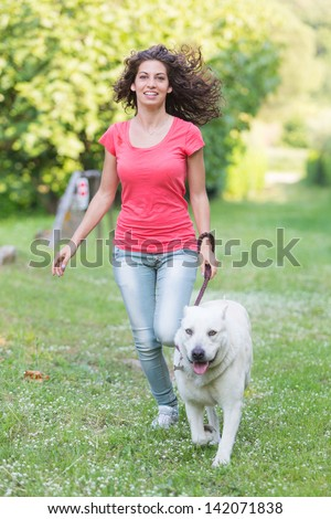 Young Woman Running with Her Dog - stock photo