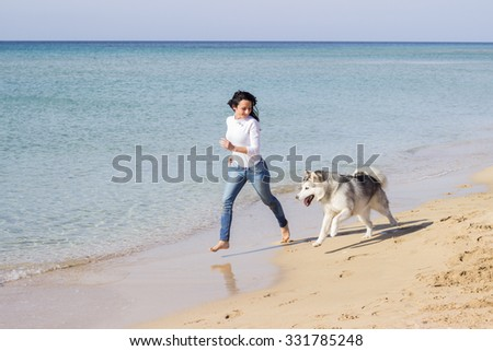 Young woman running with her husky dog on sea beach at spring