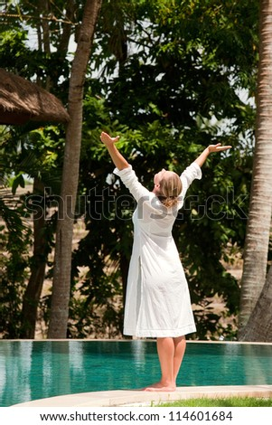 Young woman's figure with arms outstretched while standing at the edge of a swimming pool in a tropical nature location. - stock photo