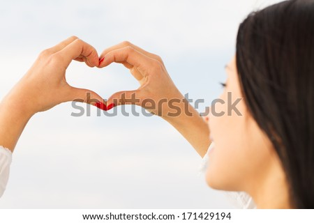 Young woman's hands forming a heart symbol.
