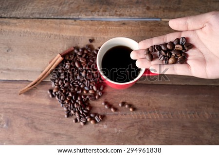 Young woman's hands holding coffee beans.vintage effect - stock photo