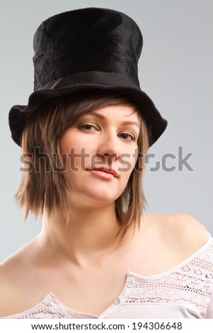 young woman's portrait wearing a  black top hat - stock photo