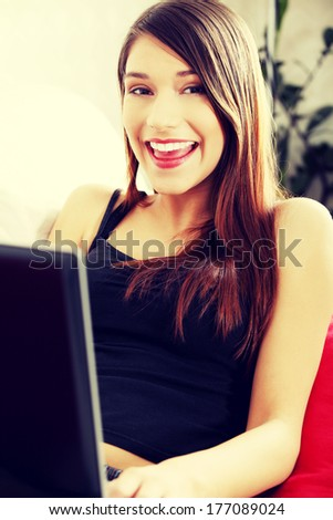 Young woman's working on laptop and smiling to camera. In home. - stock photo