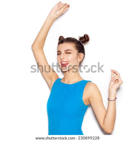 Young woman saluting and winking and showing tongue. Beauty girl with bright makeup hairstyle with horns in a blue dress having fun. On a white background, not isolated