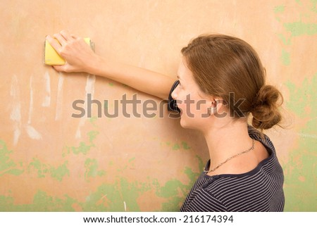 young woman sanding wall - stock photo