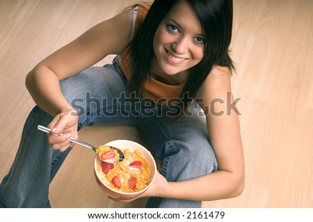 Young woman sat eating a bowl of corn flakes cereal with strawberries on top. - stock photo