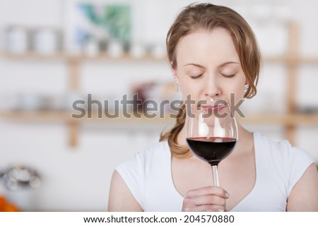 Young woman savoring the bouquet of a glass of wine as she sniffs at the glass with her eyes closed in bliss as she concentrates on the smell, with copyspace indoors in the kitchen - stock photo