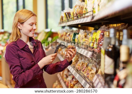 Young woman scanning barcode of bag of nuts in supermarket with her smartphone - stock photo