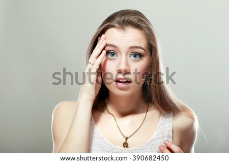 young woman scared forgetting something over grey background - stock photo