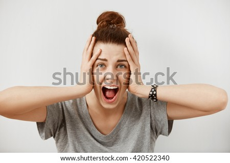 Young woman screaming in terror with hands on her head, mouth wide open looking in panic at the camera. Close up portrait of irritated female shouting, covering her ears, angry with noisy neighbours  - stock photo