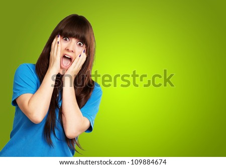 young woman screaming isolated on green background - stock photo