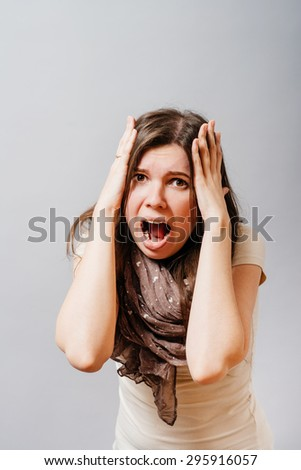 Young woman screams hands on his head. On a gray background.