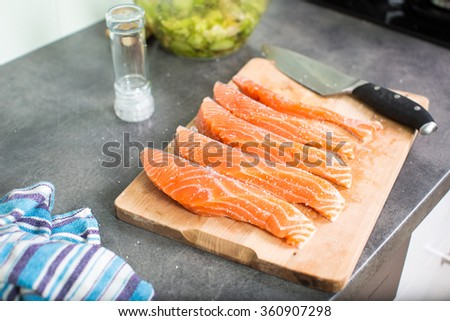 Young woman seasoning a salmon filet in her modern kitchen, preaparing a healthy food - stock photo