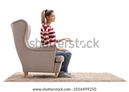 Young woman seated in an armchair talking with someone isolated on white background