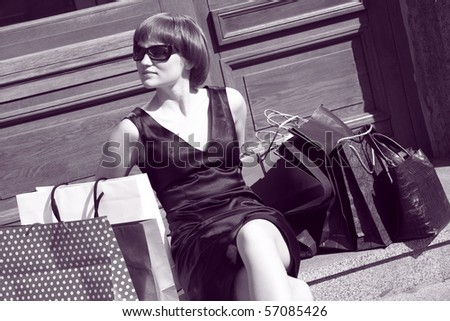 young woman seating near multicolor shopping bags