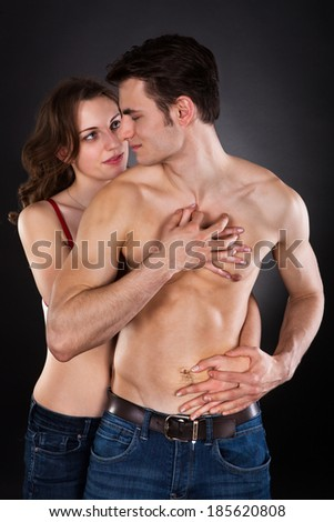 Young woman seducing man isolated over black background - stock photo