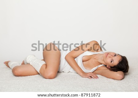 young woman seductively lying on floor. in white underwear. - stock photo