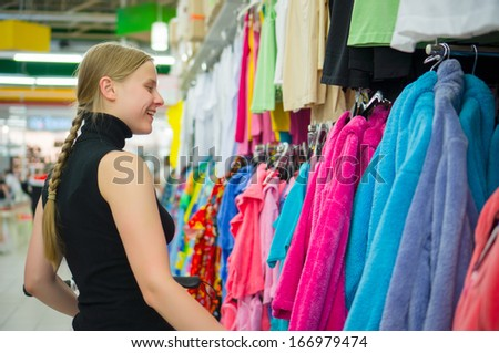 Young woman select bath clothes in supermarket